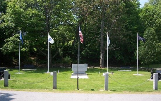 Image of five flags around a police memorial