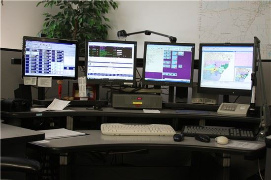 Image of 911 dispatch center desk with four screens
